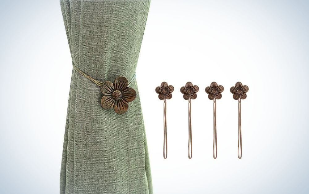 A hanging curtain with a piece of olive color and some decorative clasps in the shape of brown flowers.