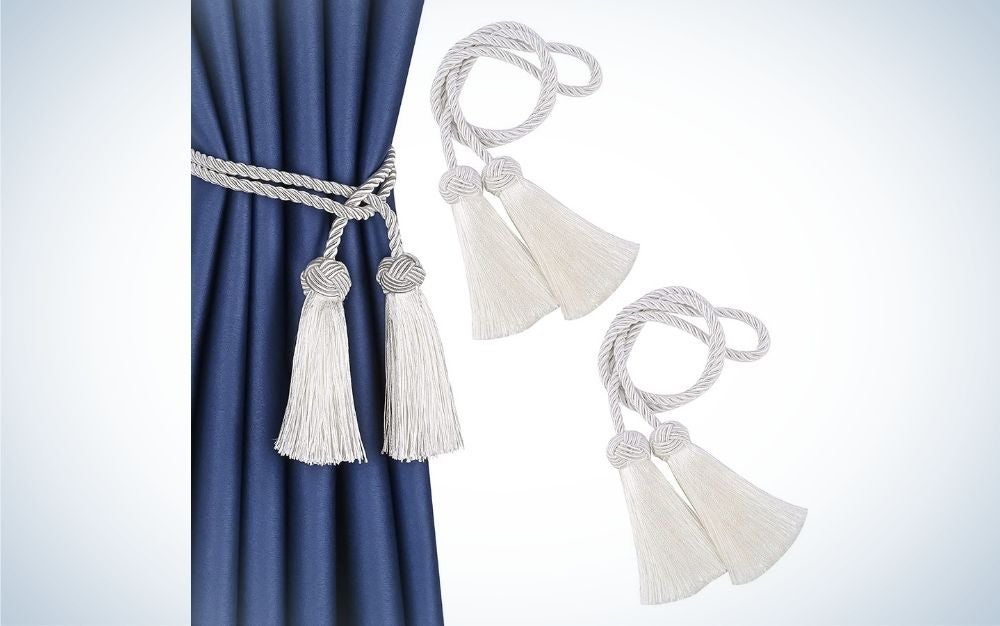 A hanging curtain with a piece of blue color as well as some decorative clasps with fringe and the three decorative clasps are in white color.