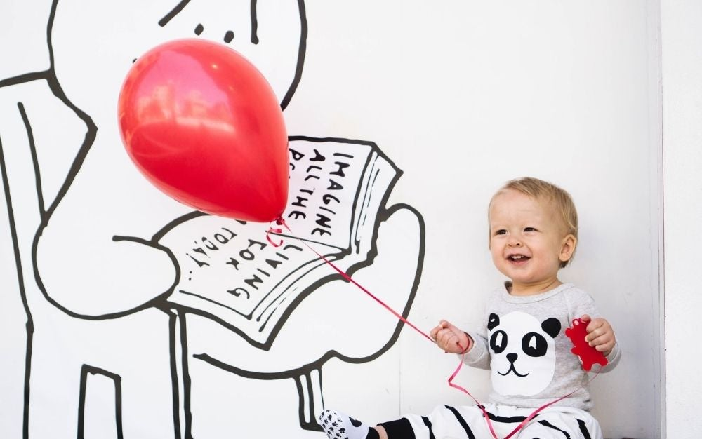 A smiling kid holding in his hands a red balloon and wearing pajamas with panda figure into it.