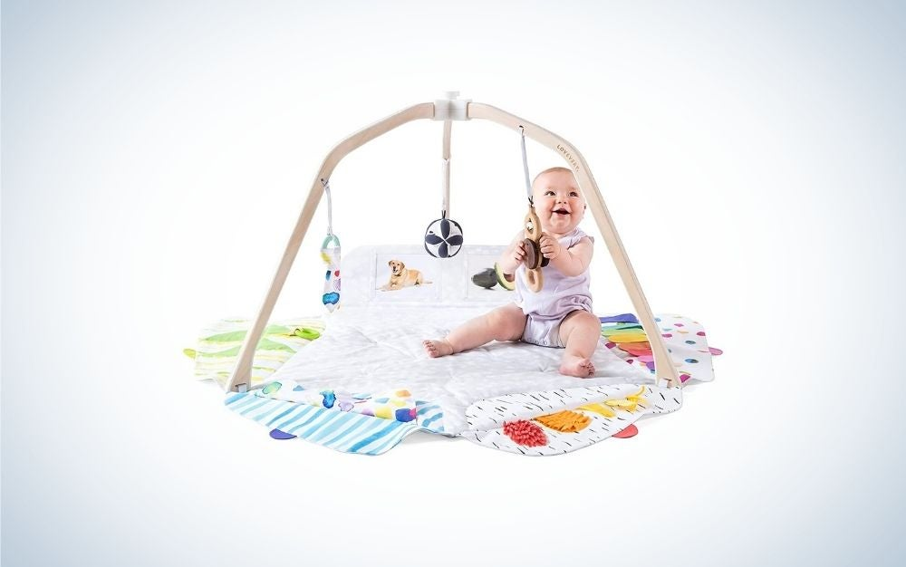A fun game for young children with a layer from below with different figures in it as well as a series of hanging toys with which the happy toddler plays below them.
