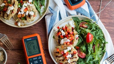 Wireless meat thermometer on a table next to two grilled chicken plates