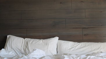 A bed with dark brown ledge and two rugged white pillows all.