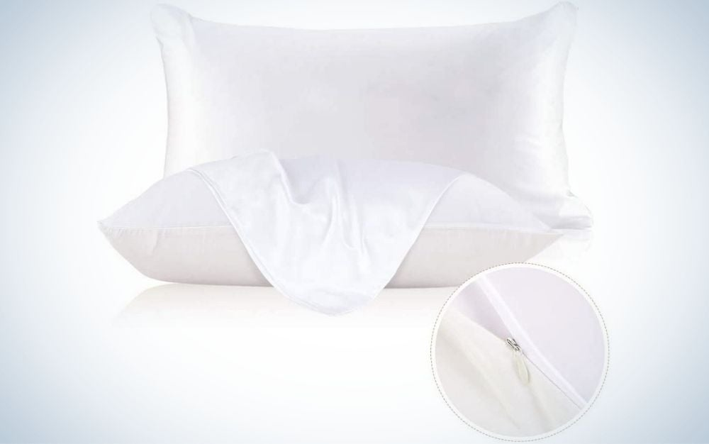 Two very white pillows in rectangular shapes, where one of them is lying down and the other on foot with a white piece from above.
