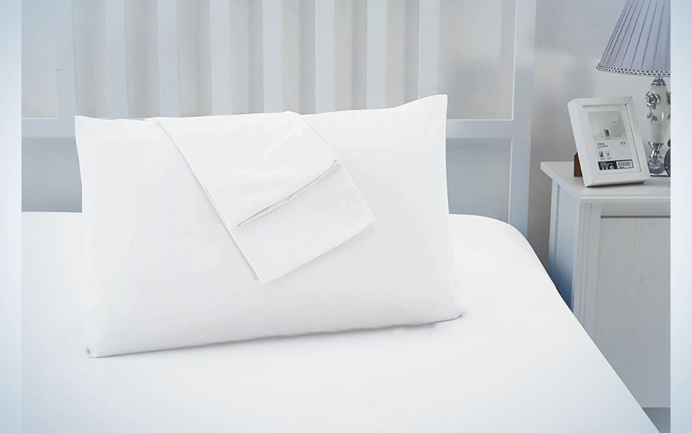 The head of a bed covered with white cover as well as a white inflated pillow over it with a white folded cover from above as well.