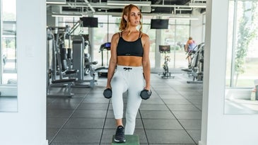 A blonde girl wearing sports clothes who is doing fitness with some weights in and around her are full of fitness equipment.