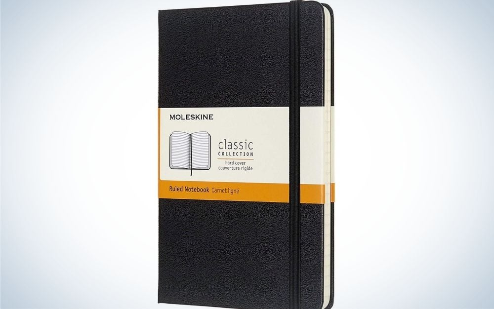 A black and white notebook in the middle with a sling that keeps the pages closed.