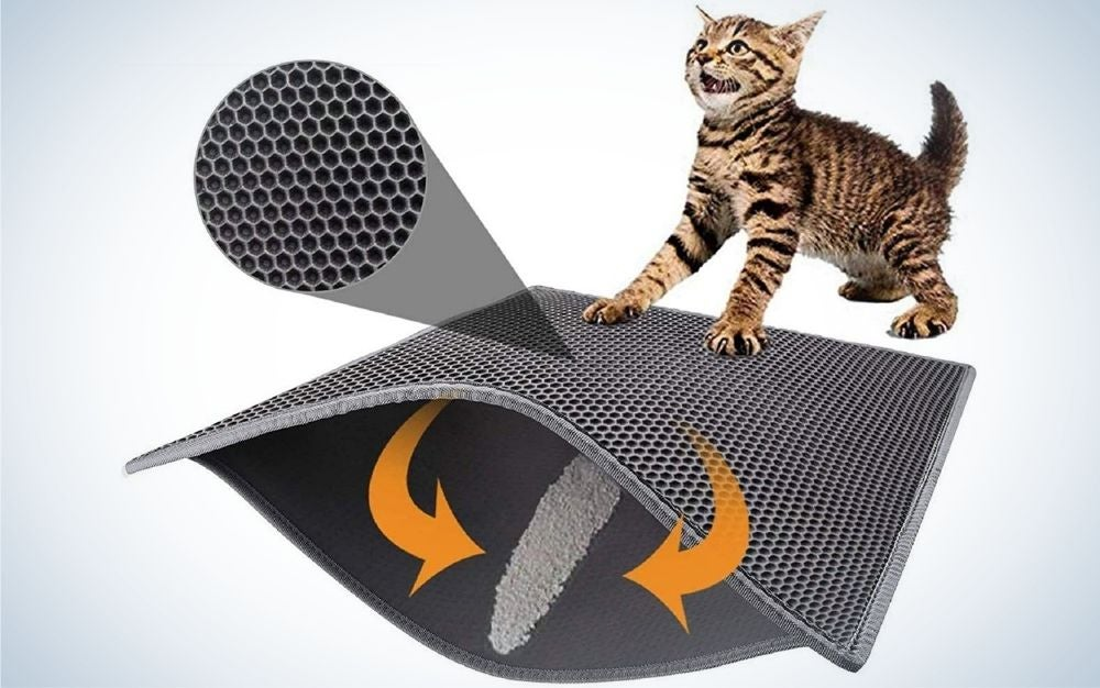 A cat who is playing by pushing with paws a square gray tape with a second layer on it.