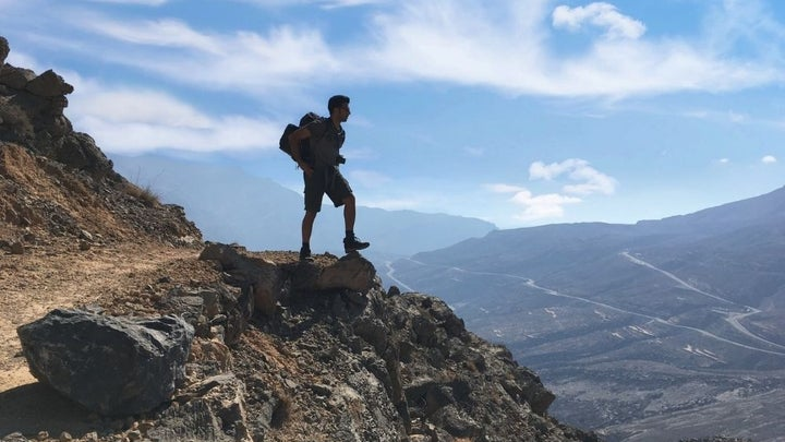 A man dressed in hiking clothes and carrying a bag in his arms is standing on a rock in the mountains.