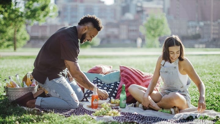 A young man in a black t-shirt and jeans and a woman in a white t-shirt, who are having a picnic together on a green space.